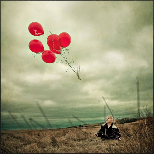 Little girl in field with red balloons