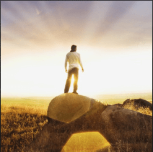 Man standing on rock facing sun